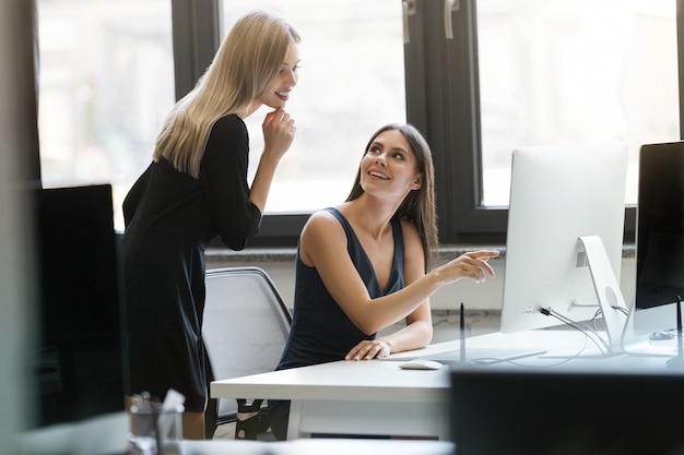 Zwei lächelnde geschäftsfrauen, die mit computer zusammen arbeiten