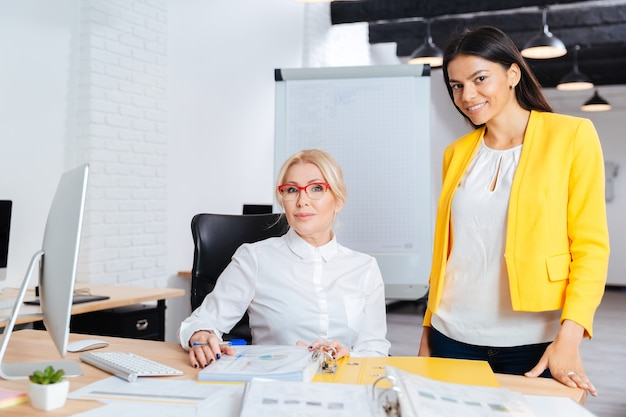 Zwei lächelnde geschäftsfrauen, die zusammen am computer am tisch im büro arbeiten