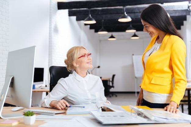 Zwei lächelnde geschäftsfrauen, die zusammen auf dem notizbuch am tisch im büro arbeiten