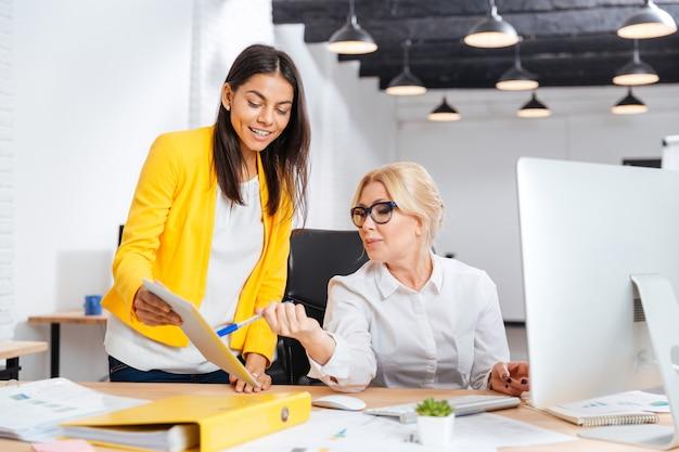 Zwei lächelnde geschäftsfrauen, die zusammen mit pc am tisch im büro arbeiten