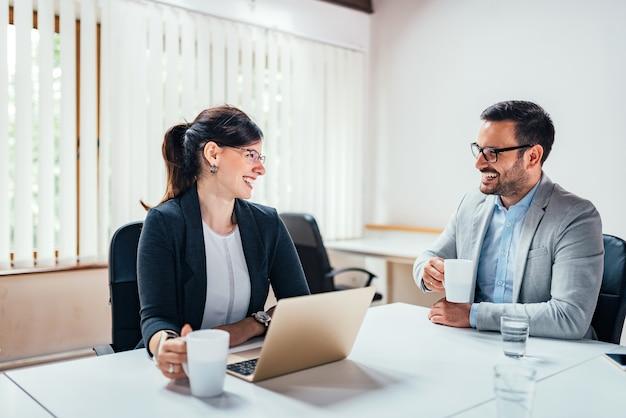 Zwei lächelnde geschäftsleute, die tee oder kaffee beim sitzen am schreibtisch trinken.