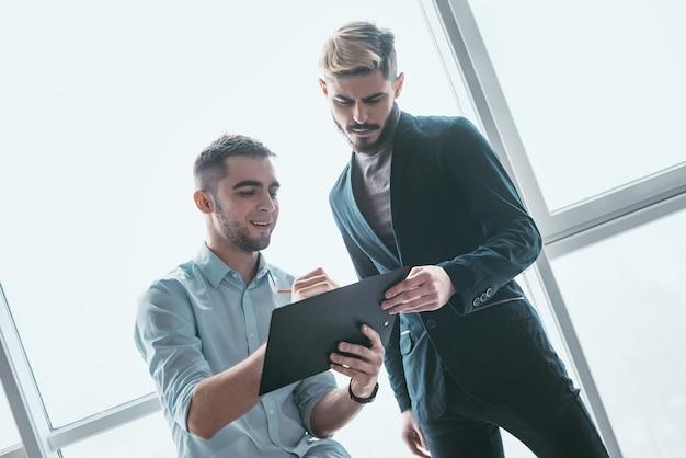 Zwei lächelnde geschäftsleute, die über förderfähige investitionen sprechen, manager, der seinem kollegen einen finanzbericht vorlegt, der gute arbeitsergebnisse zeigt, auf papier zeigt, einen deal anbietet, ein neues projekt bespricht