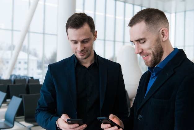 Zwei lächelnde geschäftsleute im flughafen, die wichtiges projekt besprechen und telefonbildschirm betrachten.