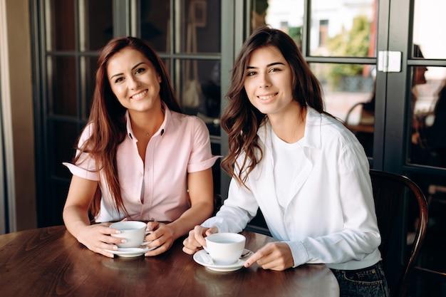 Zwei lächelnde geschäftsmädchen, die tee während des business-lunchs trinken