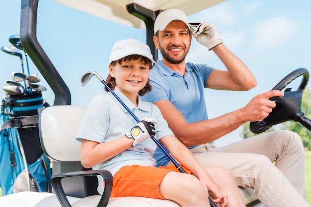 Zwei lächelnde golfer. glücklicher junger mann und sein kleiner sohn sitzen im golfwagen und schauen in die kamera