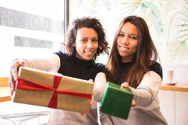 Zwei lächelnde hispanische mädchen zeigen ein geschenk. sie sind in einem café.