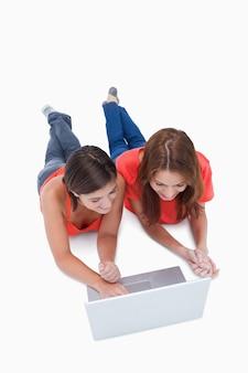 Zwei lächelnde jugendlichen, die sich beim betrachten eines laptops hinlegen