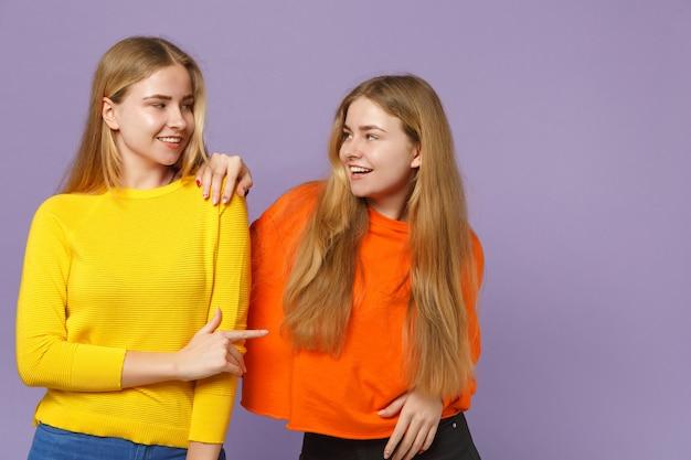 Zwei lächelnde junge blonde zwillingsschwestern mädchen in bunten kleidern, die sich gegenseitig ansehen und den zeigefinger einzeln auf violettblauer wand zeigen. menschen-familien-lifestyle-konzept.