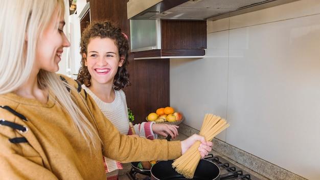 Zwei lächelnde junge frauen, die zu hause spaghettis kochen
