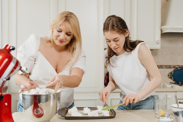 Zwei lächelnde junge frauen legen fleißig das geschlagene baiser mit einem löffel und einem schulterblatt in der küche auf ein tablett. mädchen bereiten sich darauf vor, eine köstliche zitronenbaisertorte zu kochen.