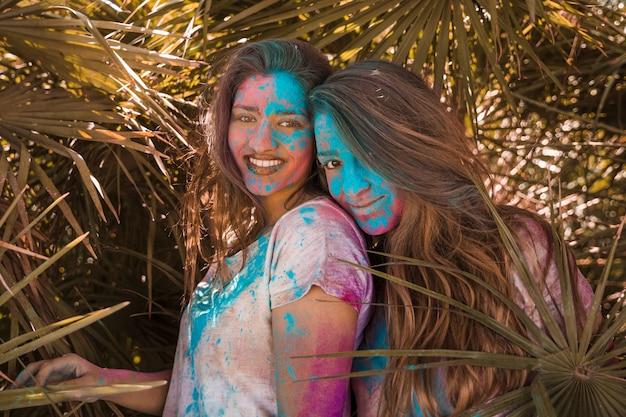 Zwei lächelnde junge frauen mit holi farbe auf ihrem gesicht, das kamera betrachtet