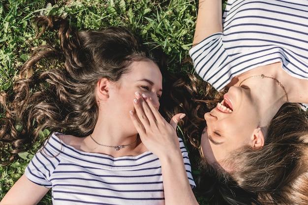 Zwei lächelnde junge freundinnen, die spaß im park haben