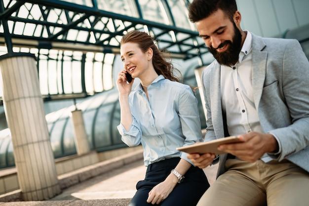 Zwei lächelnde junge geschäftsleute, die an tablet arbeiten und etwas diskutieren, während sie im freien sitzen