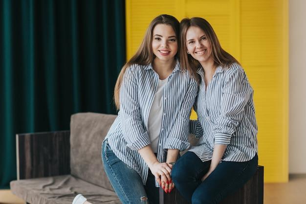 Zwei lächelnde junge mädchen in gestreiften hemden, jeans und turnschuhen, die auf der couch aufwerfen