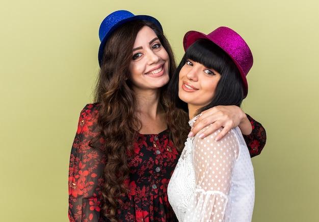 Zwei lächelnde junge partyfrauen, die einen partyhut tragen, einer hält einen anderen an der schulter, beide schauen nach vorne isoliert auf olivgrüner wand?