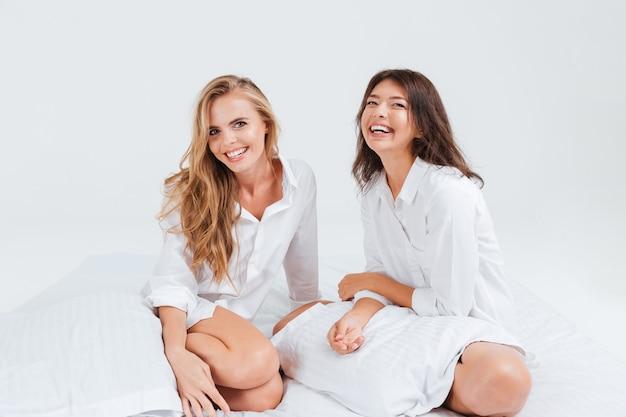 Zwei lächelnde junge sexy mädchen, die auf dem weißen bett sitzen