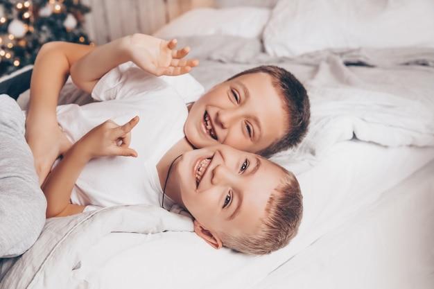 Zwei lächelnde kinder, die spaß haben, auf dem weißen bett mit weihnachtsbaum lachen und umarmen