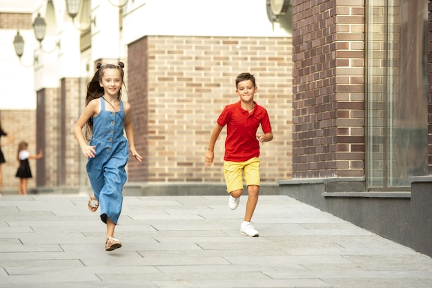 Zwei lächelnde kinder, junge und mädchen, die am sommertag zusammen in der stadt laufen?