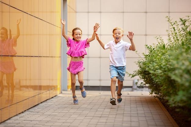 Zwei lächelnde kinder, junge und mädchen, die zusammen in der stadt laufen, stadt am sonnigen tag.