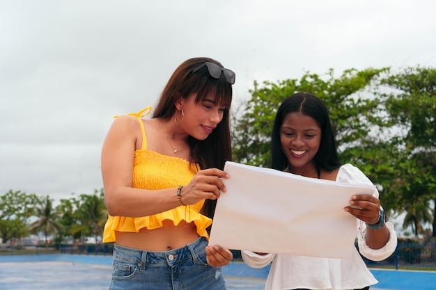 Zwei lächelnde latina-freunde mit einer karte im freien