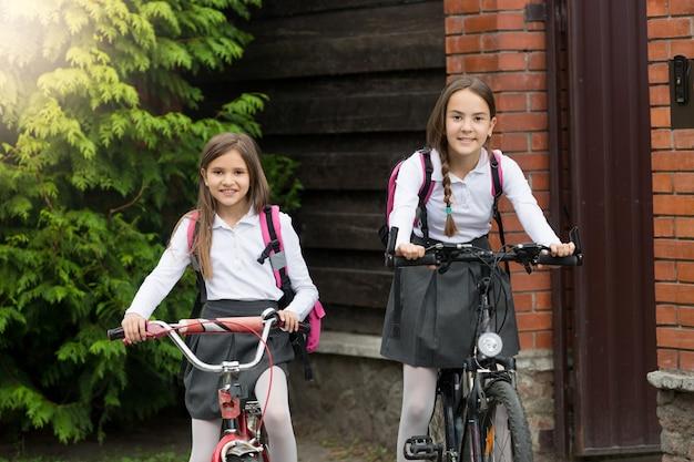 Zwei lächelnde mädchen, die auf fahrrädern zur schule gehen