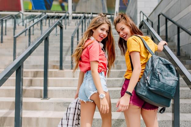 Zwei lächelnde mädchen, die jeansshorts und stilvolle armbanduhr tragen, die von hinten auf der treppe aufwirft