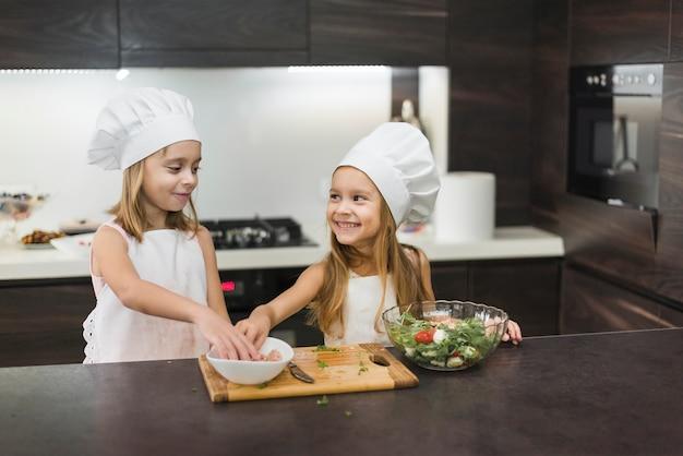 Zwei lächelnde mädchen, die lebensmittel in der küche zubereiten