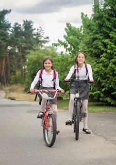 Zwei lächelnde mädchen, die mit dem fahrrad zur schule fahren