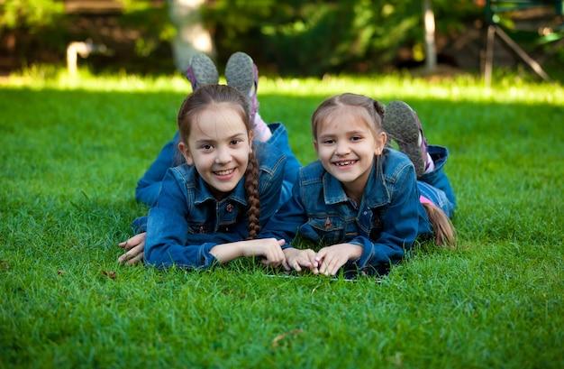 Zwei lächelnde mädchen mit tablet beim liegen auf gras im hof grass