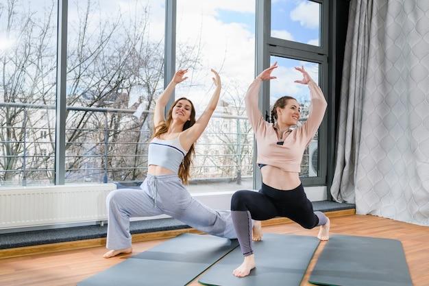 Zwei lächelnde mädchen stehen auf der matte vor dem panoramafenster, strecken die beine und heben die hände hoch, gesunde übungen