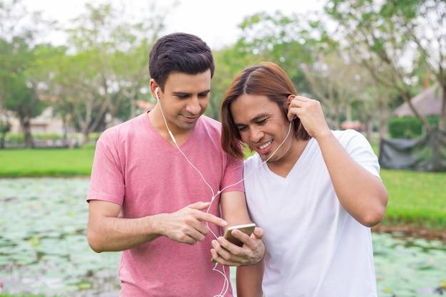 Zwei lächelnde männer, die musik im park hören