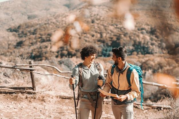 Zwei lächelnde männer, die sprechen, während sie im herbst in der natur stehen. ein mann hält karte, während ein anderer stöcke hält wandern im herbst in der natur.
