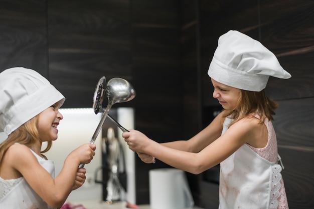 Zwei lächelnde nette schwestern in den hüten des chefs kämpfen mit küchengerät