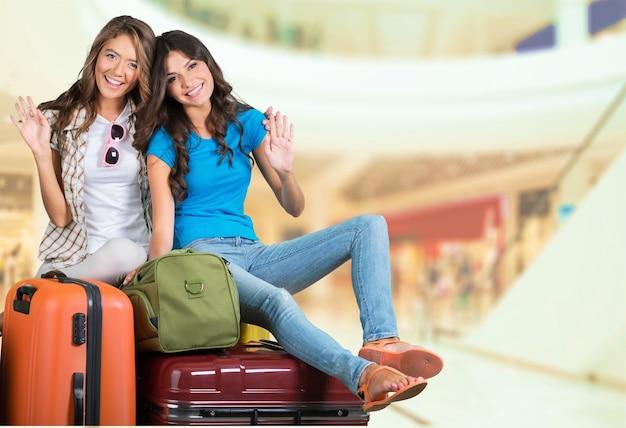Zwei lächelnde schöne frauen auf kofferstapel im flughafen, reisekonzept