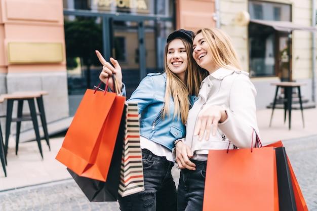 Zwei lächelnde schöne frauen beim einkaufen mitten auf der straße stehen, eine von ihnen zeigt mit der hand in richtung geschäfte