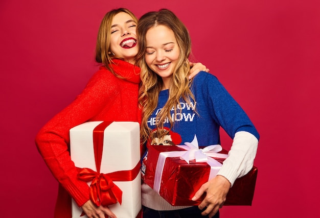 Zwei lächelnde schöne frauen in stilvollen pullovern mit großen geschenkboxen