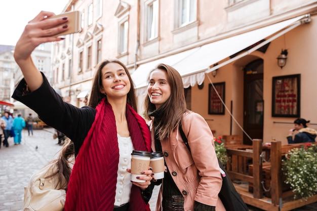 Zwei lächelnde schöne junge frauen, die selfie mit handy in der altstadt machen