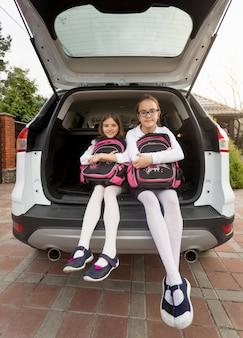 Zwei lächelnde schulmädchen sitzen im offenen kofferraum mit schulranzen