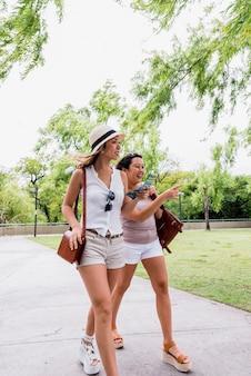 Zwei lächelnde stilvolle junge frauen, die zusammen in den park gehen