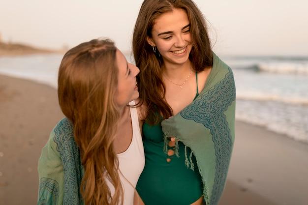 Zwei lächelnde weibliche freunde, die am strand genießen