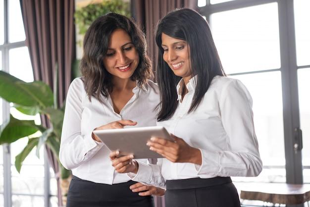 Zwei lächelnde weibliche kollegen, die nachrichten auf tablette im café lesen.