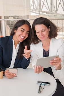 Zwei lächelnde weibliche partner, die geräte im modernen café verwenden