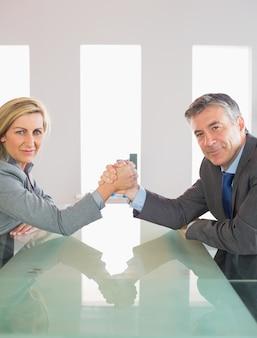 Zwei lächelnde wirtschaftler, die einen showdown haben, der um eine tabelle sitzt