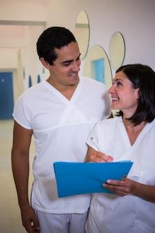 Zwei lächelnde zahnärzte mit patienten berichten