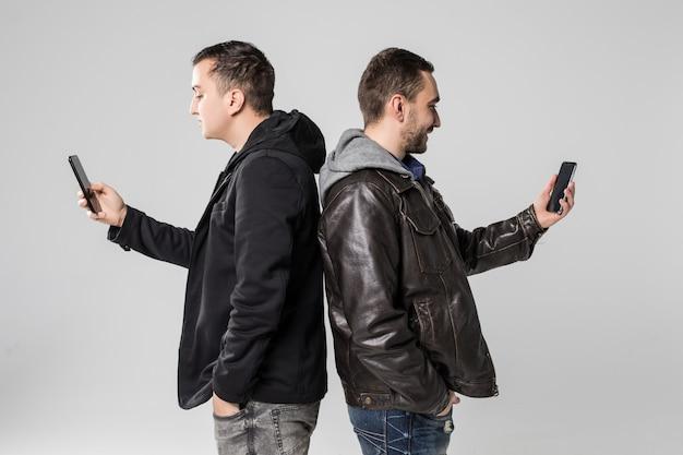 Zwei lässige hübsche mann, die nebeneinander mit telefonen in den händen lokalisiert auf weißem hintergrund stehen