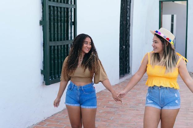Zwei lateinamerikanische mädchen, die die straße entlang gehen