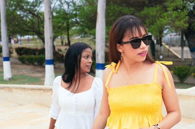 Zwei latina-freunde, die zusammen in einem park spazieren gehen