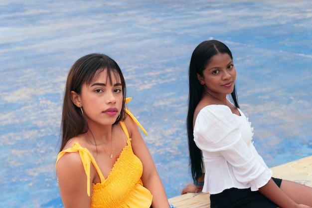Zwei latina-freunde sitzen im park und schauen in die kamera