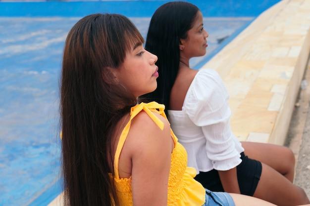 Zwei latina-freunde sitzen im park