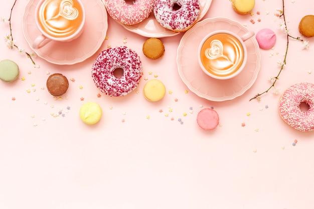 Zwei latte kaffeetassen, köstliche rosa donuts mit streusel und bunte helle macarons